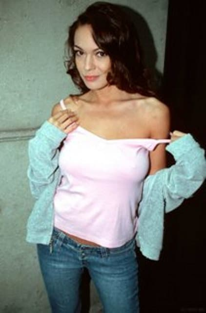 Nancy standing up in white top and blue jeans pulling on shirt straps.