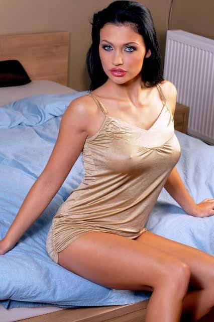 Evette sitting up on the bed in gold night slip.