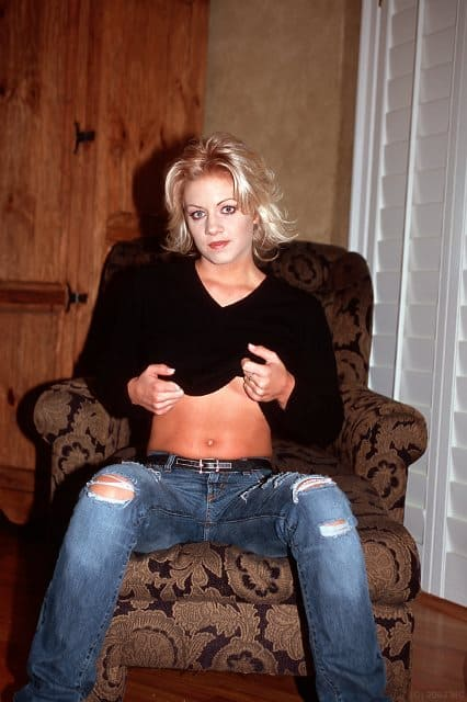 Crystal sitting down in blue jeans and black sweater.